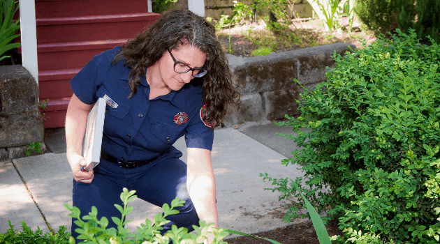 Fire department employee inspecting landscaping for flammability