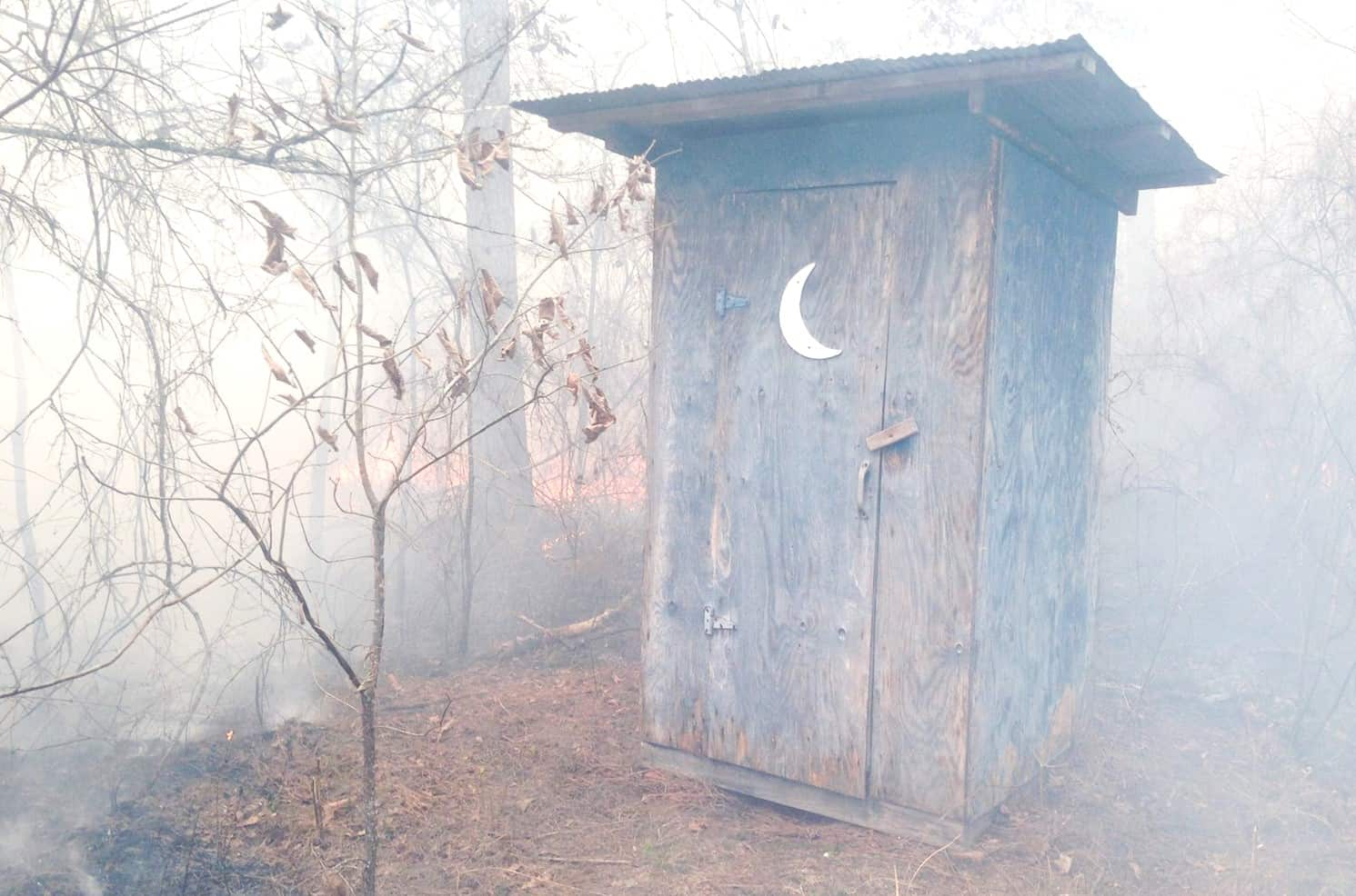 Prescribed fire behind an outhouse on private property