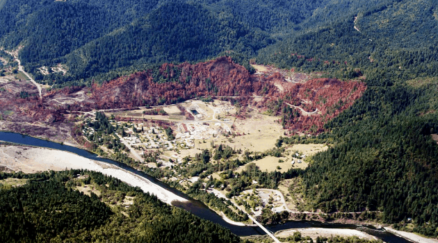 Ariel view of a community along a river, surrounded by a burnt forest