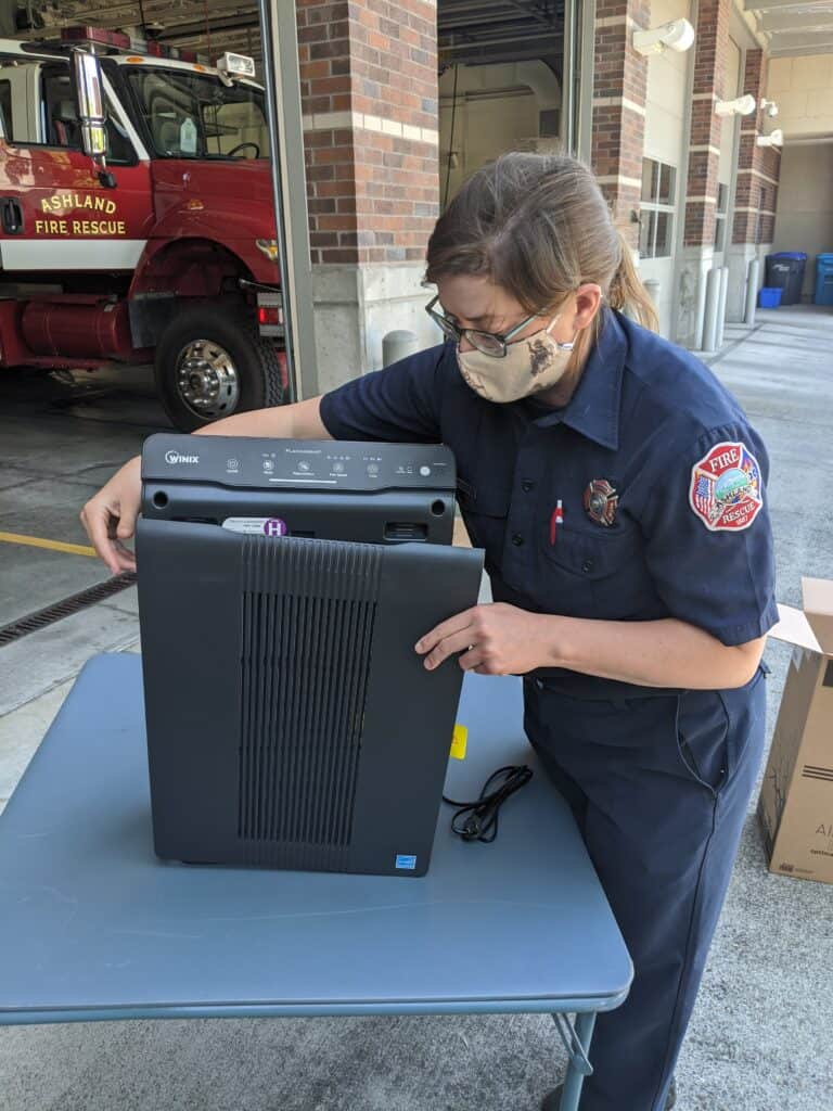 Firefighter Katie Gibble inspects the air purifier unit out front of firehouse.