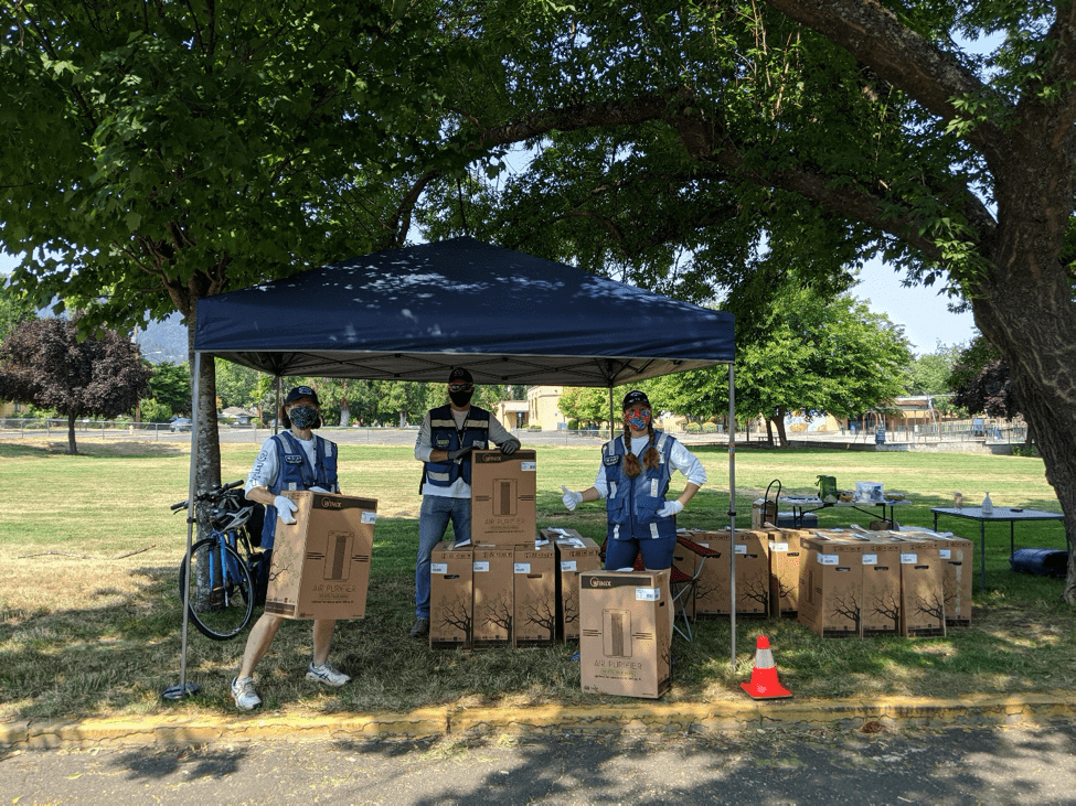 Three people in masks stand under a tent holding air purifiers.