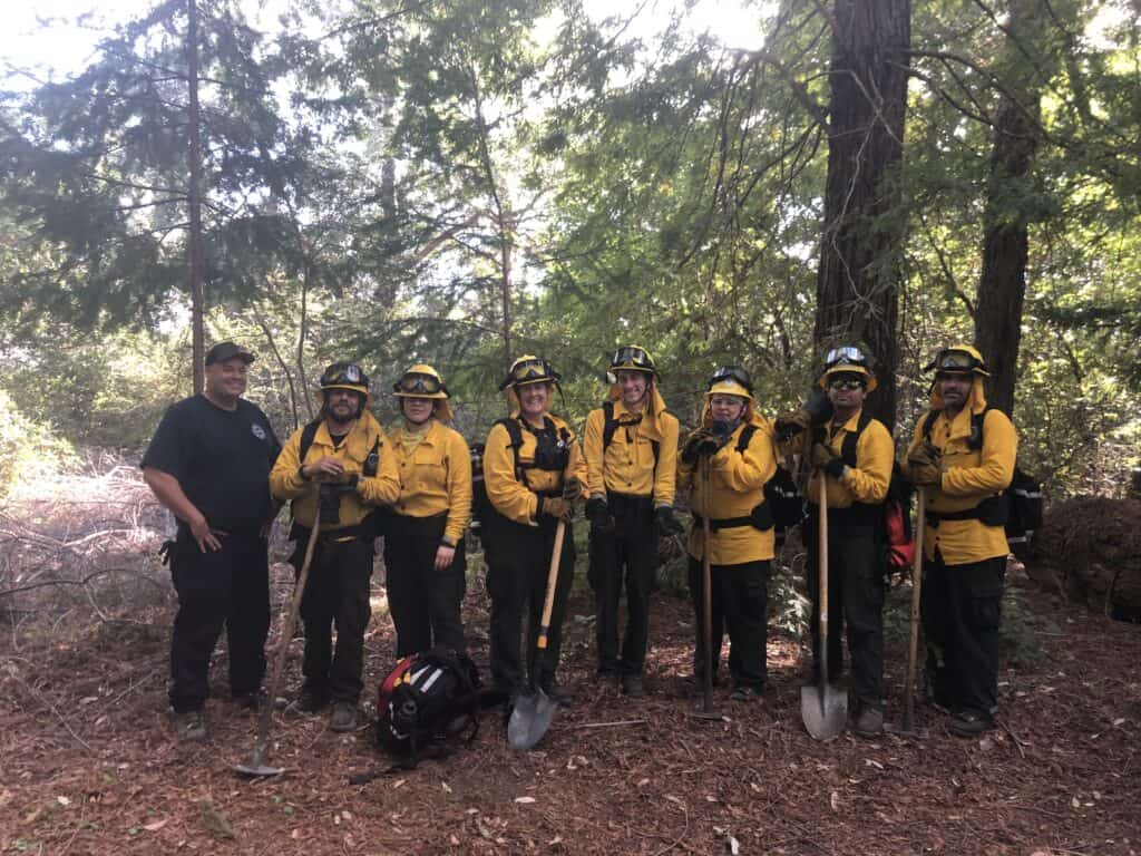 A group standing in the woods after a prescribed fire