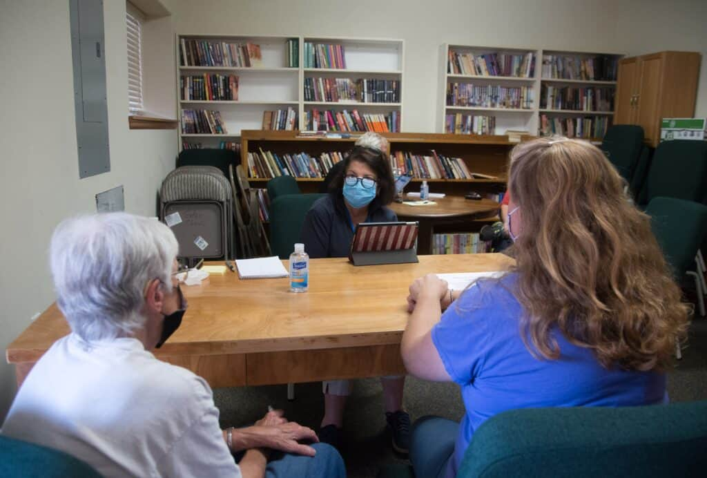 Two women meet with a FEMA volunteer at a table in a library