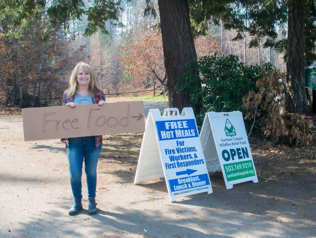 Woman standing holding sign that reads Free Food and two other signs next to her.
