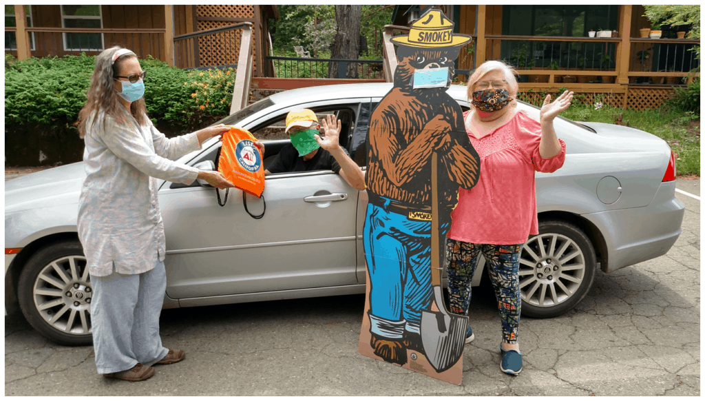 Man in car, woman stands with Smokey the Bear, and a third woman hands the man a backpack.