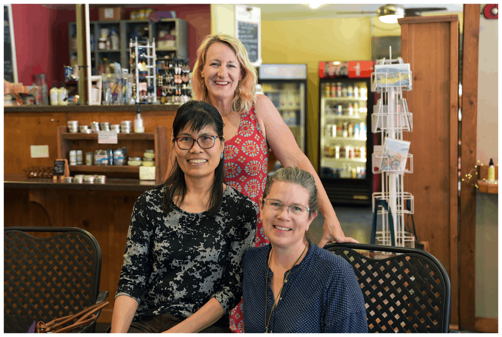 Three woman pose in a coffee shop