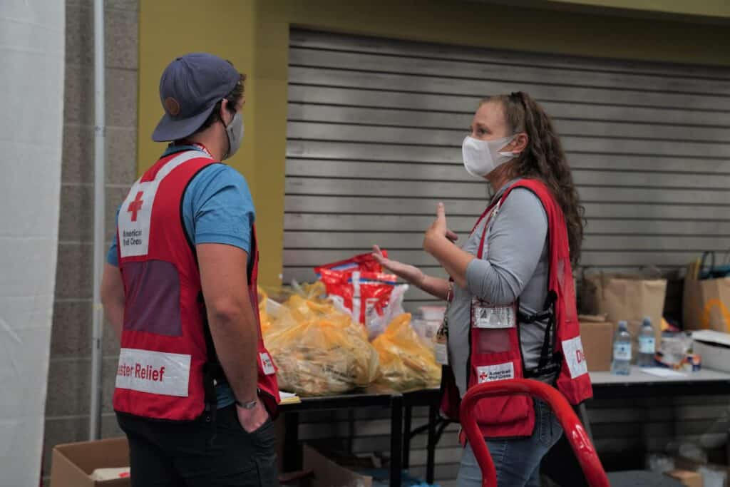 A man and a woman in Red Cross vests sort food on a table
