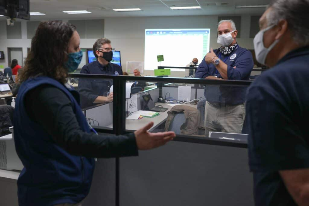 A group of people in masks standing in a office talking.