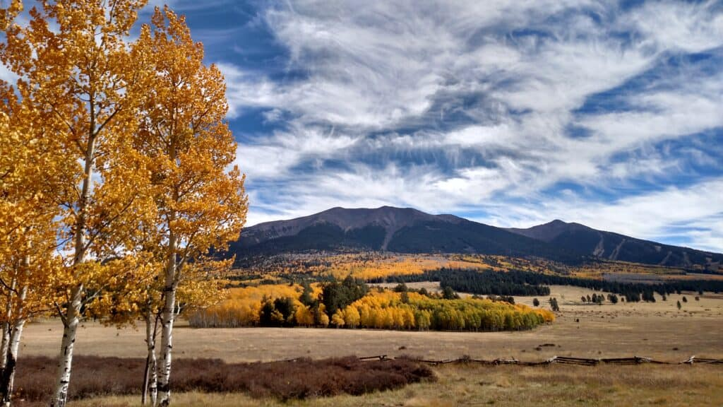 Photo depicts mountains and outdoor scene with autumn colors