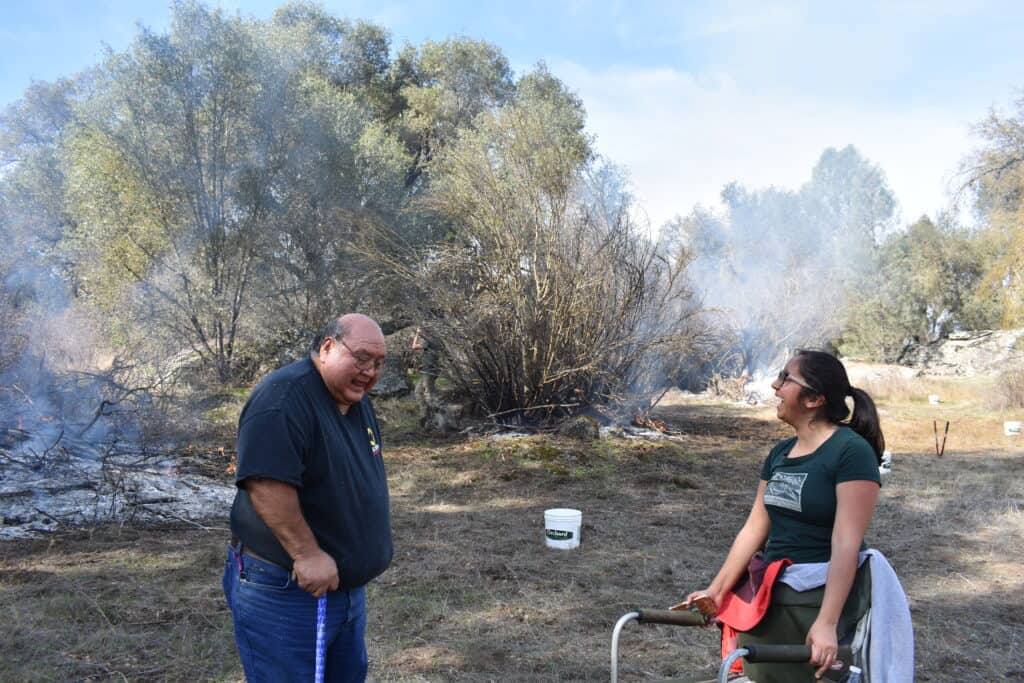 An older man and a younger woman laugh while they stand together in a field while smoke billows behind them.