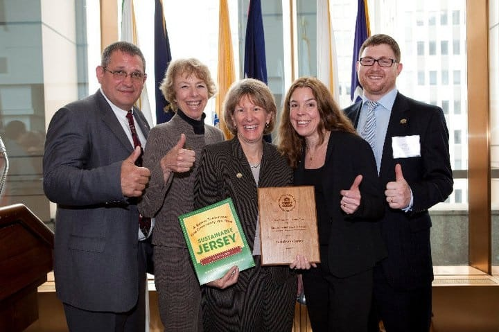A group of people posing and smiling holding plaques