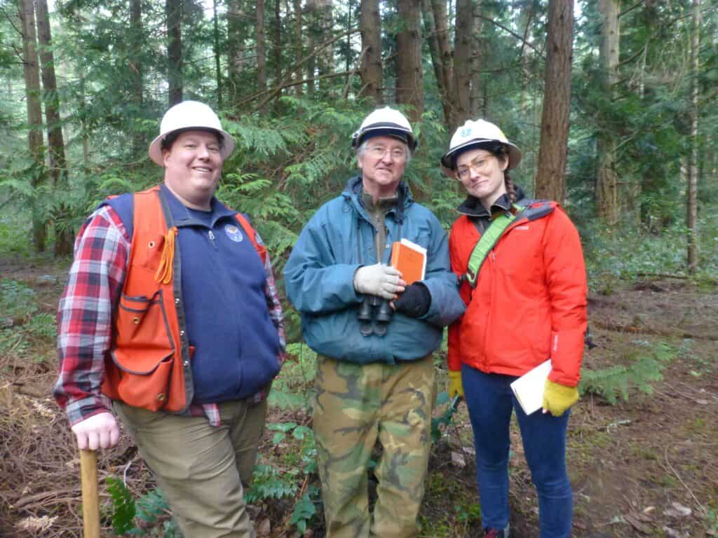 Three people in hardhats in the forest