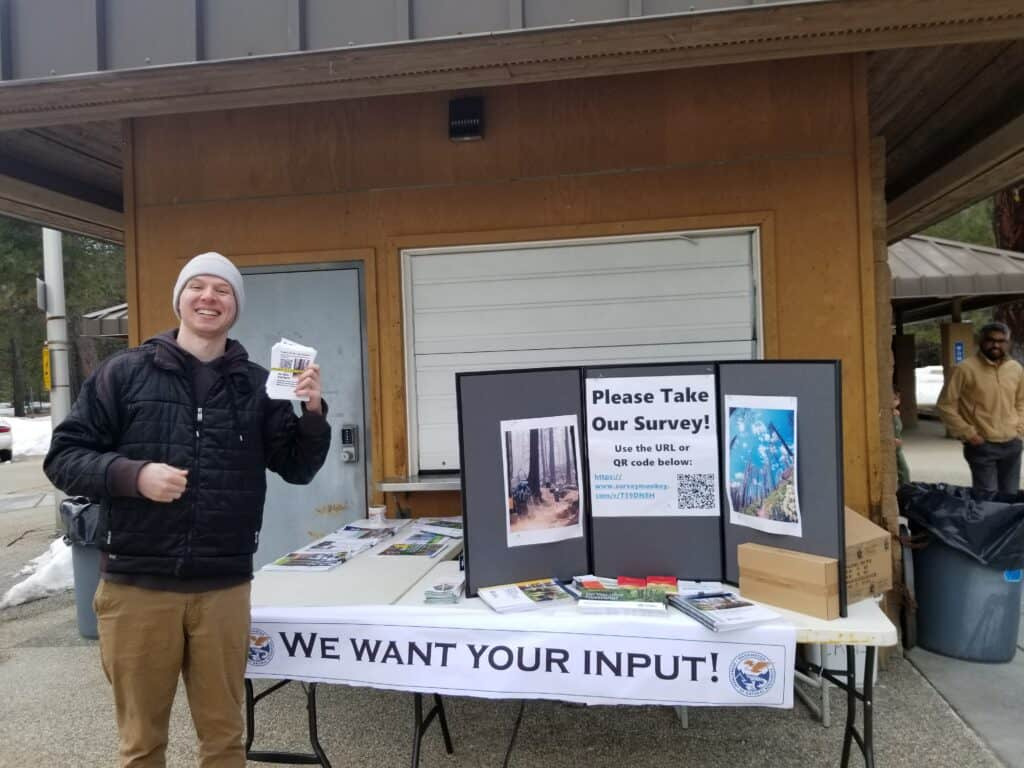 A man holds brochures in front of a display outside at a rest stop.