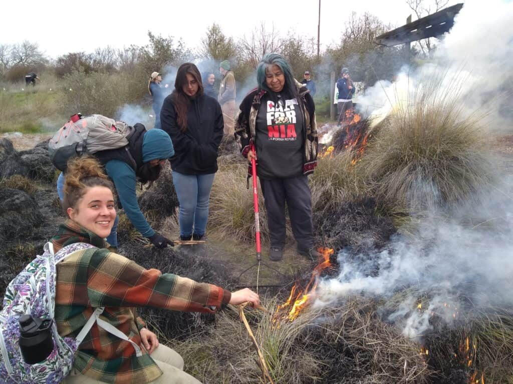 A group of people gather around a burning grass area
