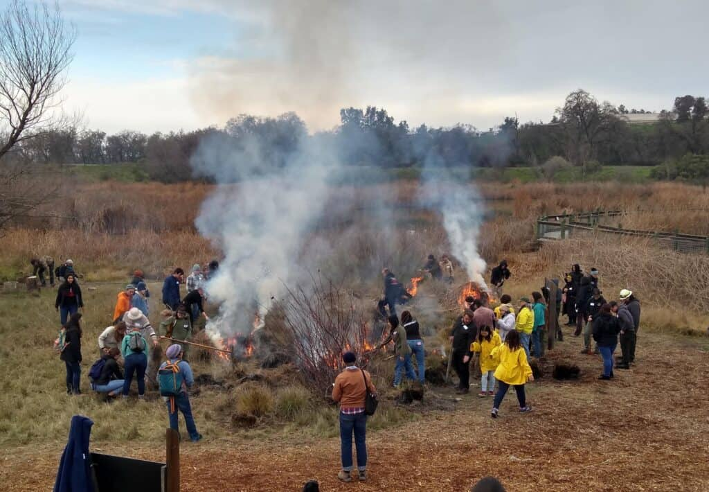 A group of people gather around a burning deergrass