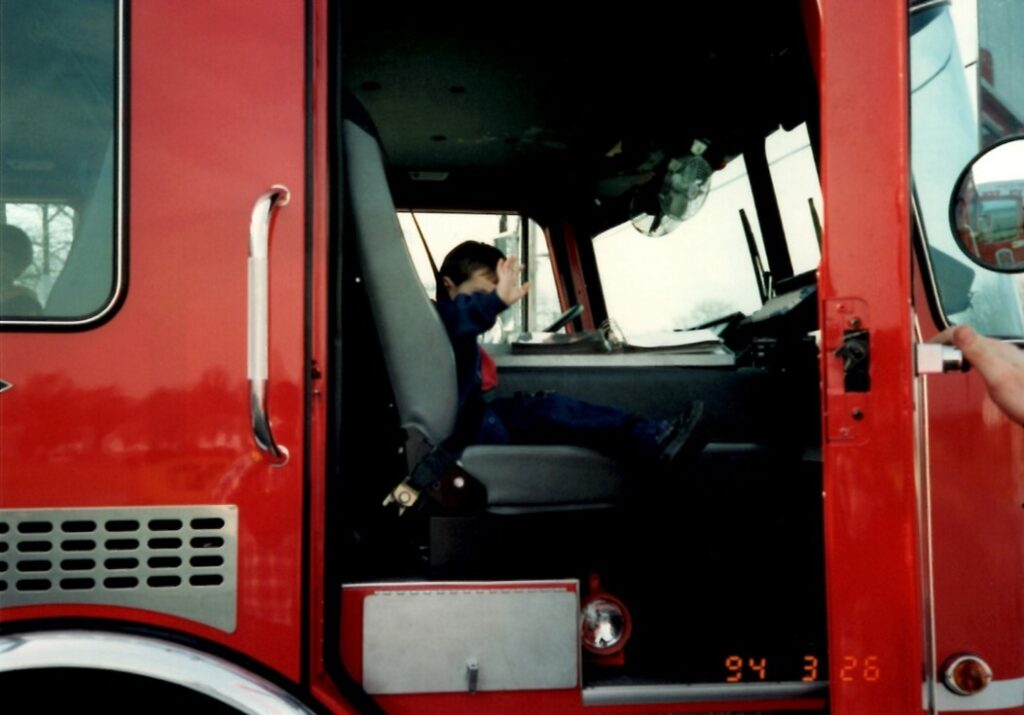 A little boy waves from the seat of a fire truck