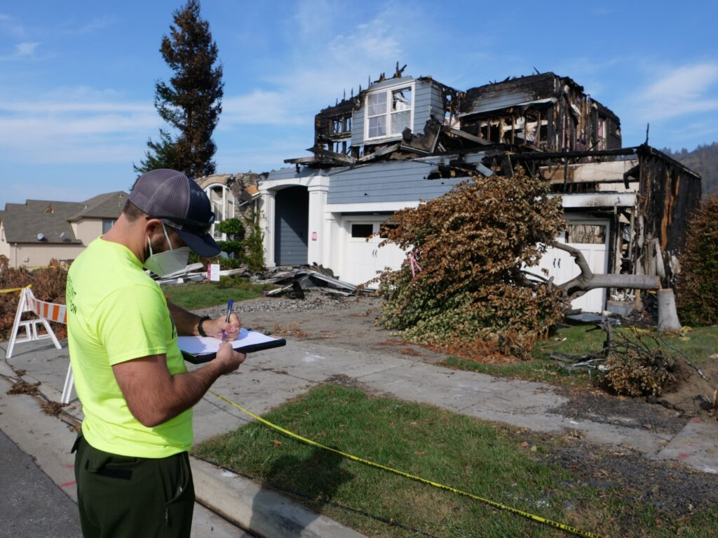 A man writes on a clipboard while in front of a burned house