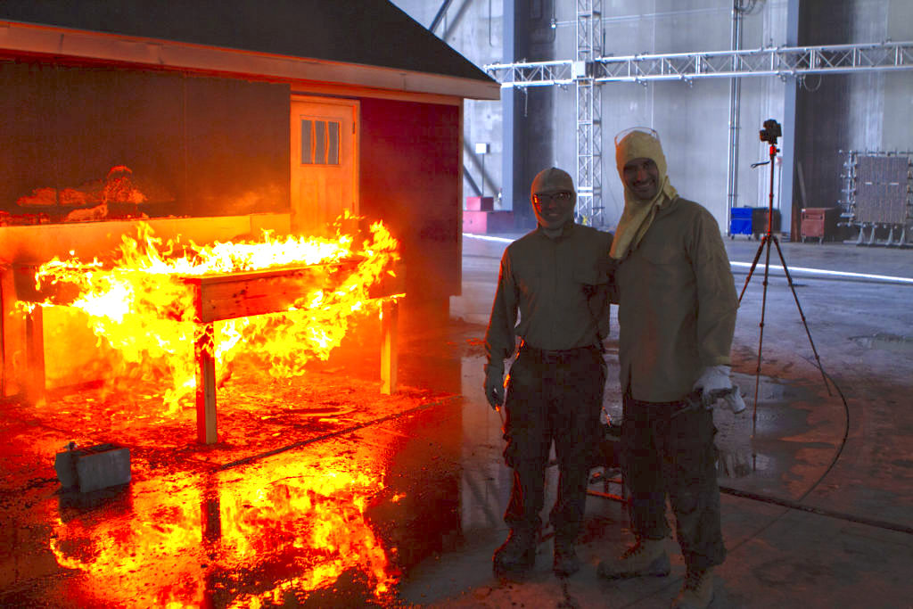 Two men stand next to a fire in the research lab