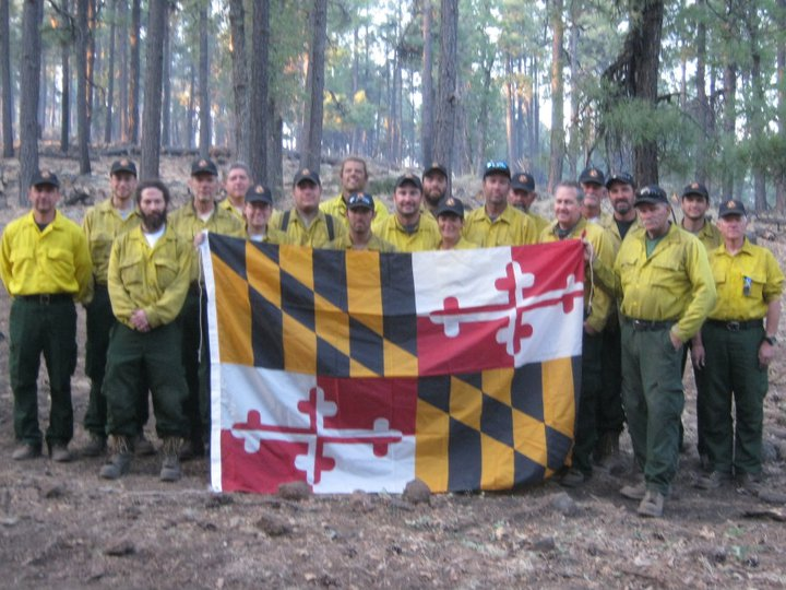 A Group of fire personnel pose with the Maryland state flag