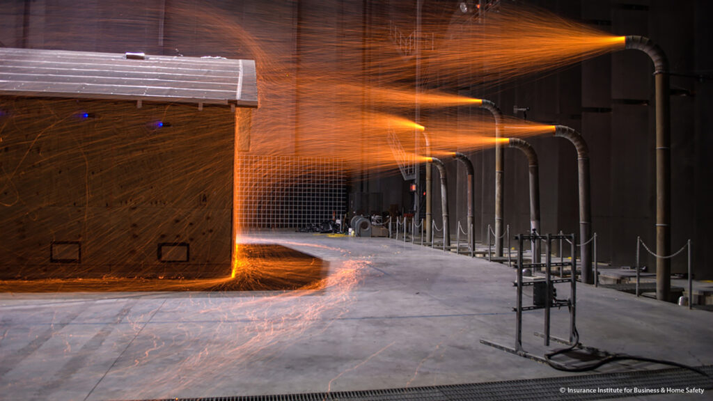 Fire embers spray onto a house from fire ember hoses in the IBHS research lab