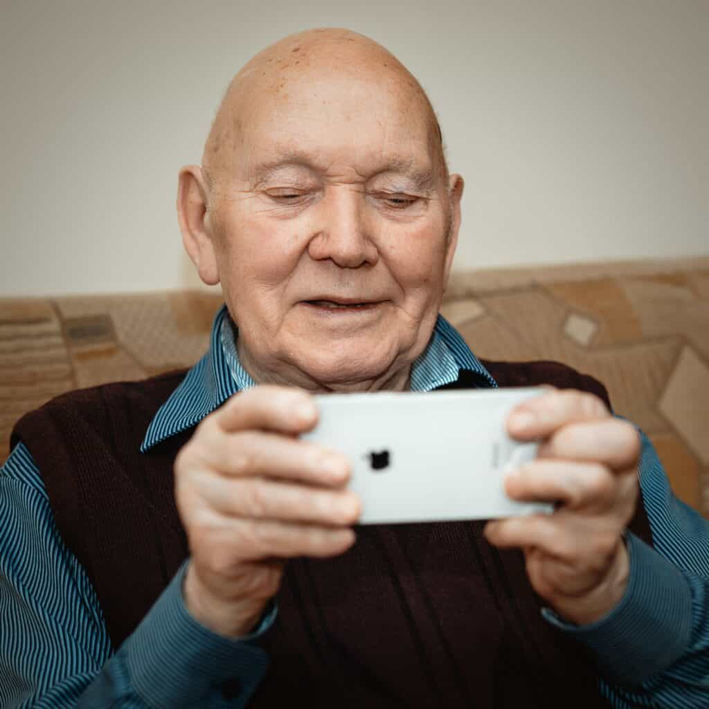 An older man holds an iPhone out in front of him