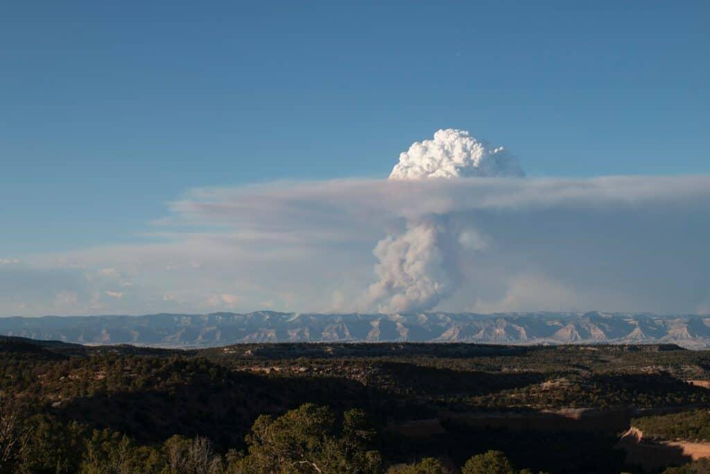 Smoke billows up behind a mountain range