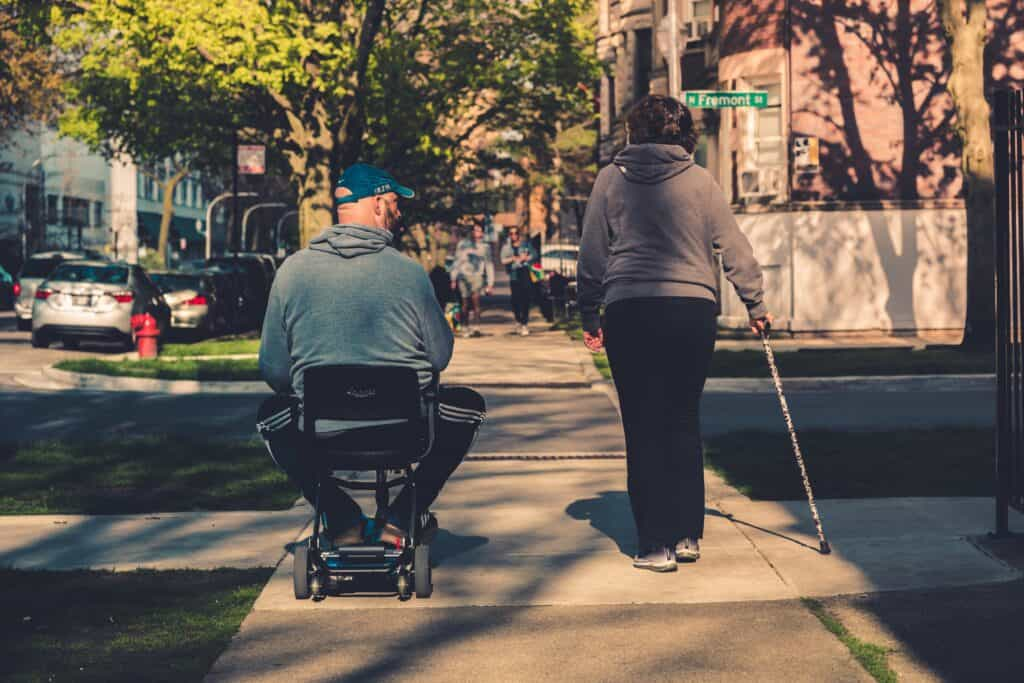 A woman with a cane walks next to a man in motorized wheelchair on a sidewalk