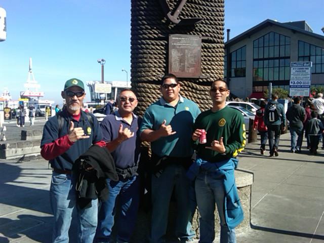 four men pose outside