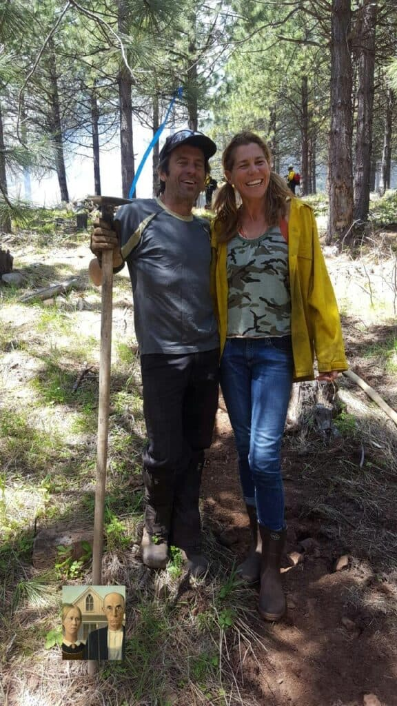 A photo of a man with a shovel and woman in the forest