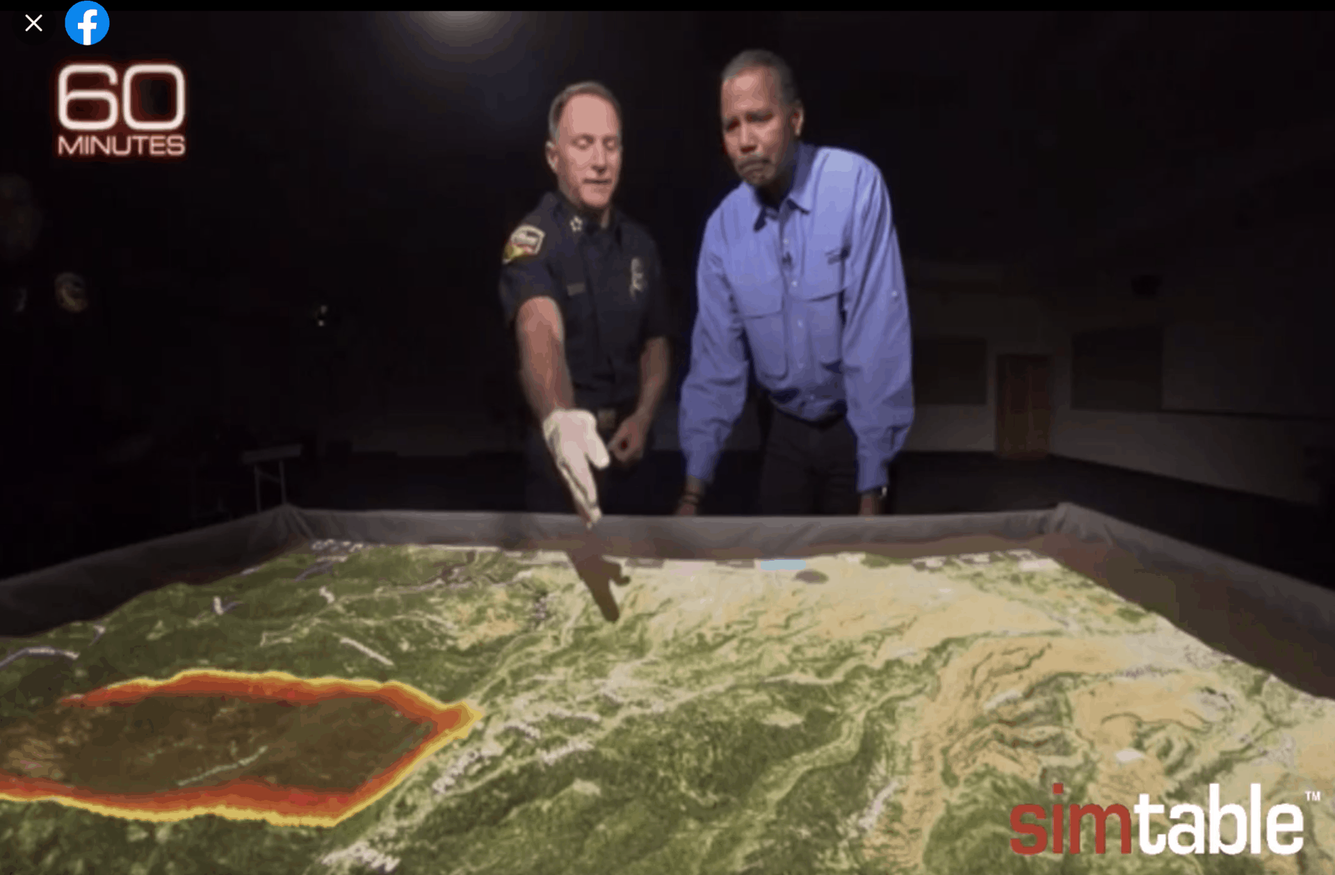 A man in uniform points out a spot on a sand table simulation to another man.