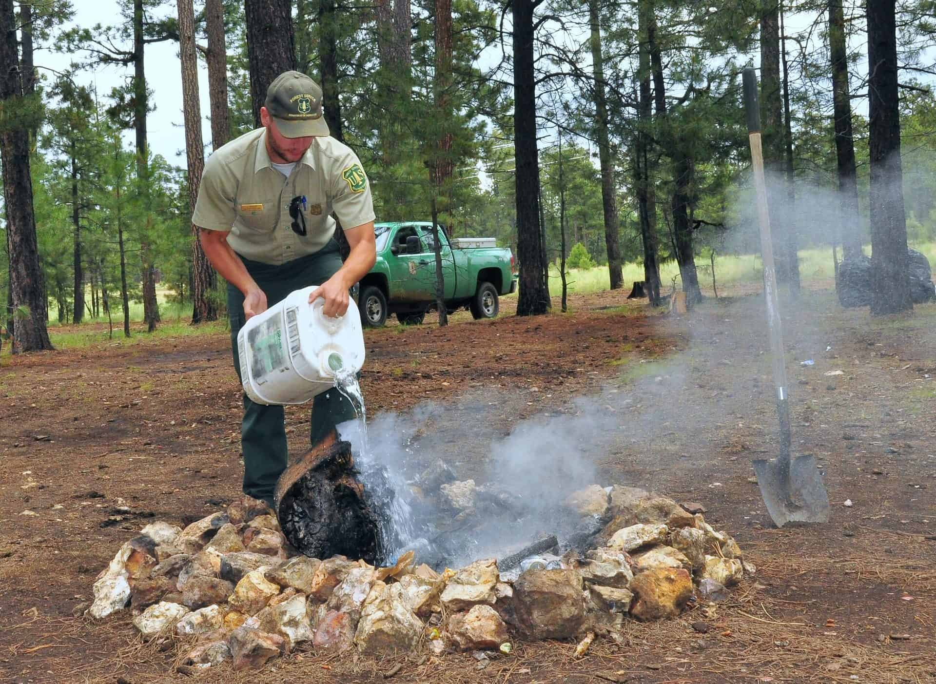 A forest service ranger dumps water from a gallon jug on a smoldering campfire