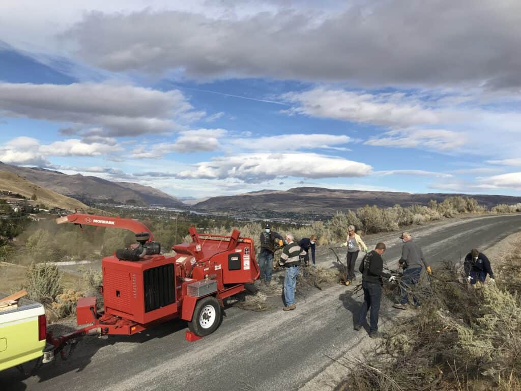 Seven people along a dirt road load clippings into a chipper