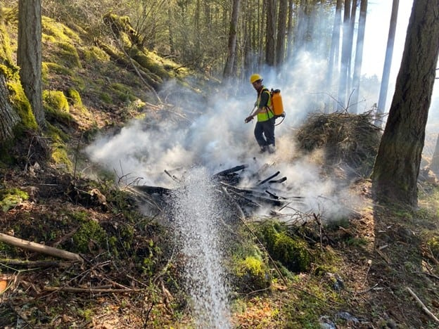 A photo of a fire fighter using a water backpack to extinguish a smoking fire