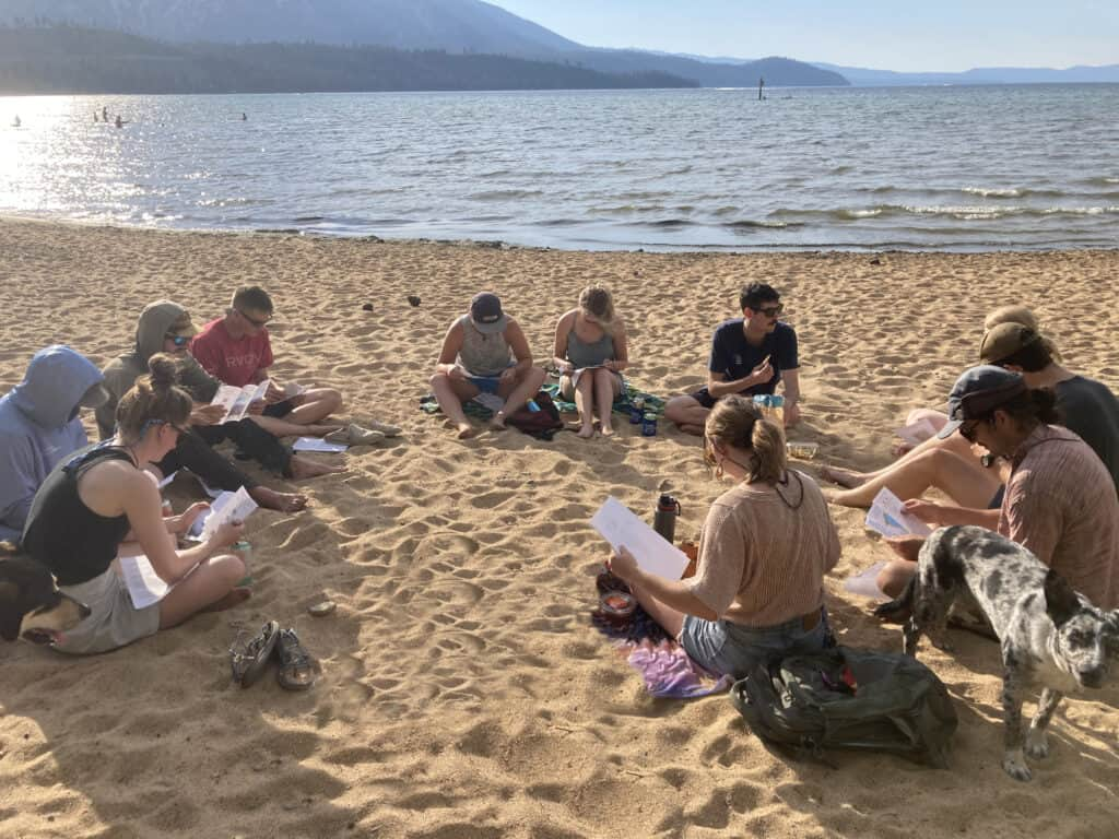 A group of people sit in a circle on the sand looking at papers with Lake Tahoe in the background