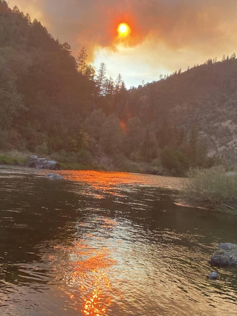 Sun with smokey haze above a river valley